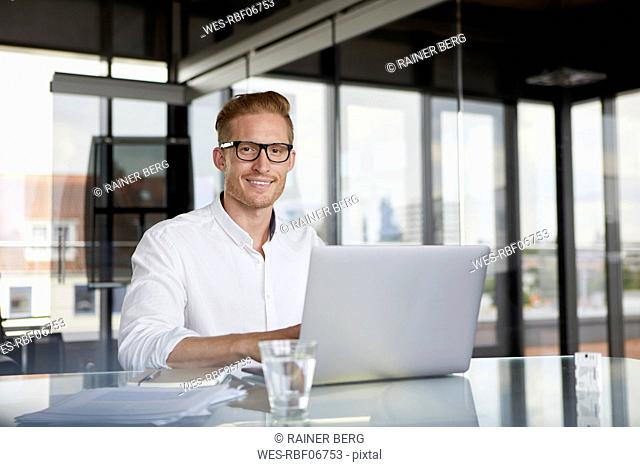 Portrait of smiling businessman using laptop on desk in office