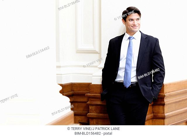 Hispanic businessman leaning in ornate hallway