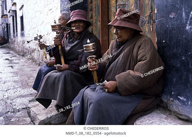 Side profile of three senior women holding prayer wheels, China