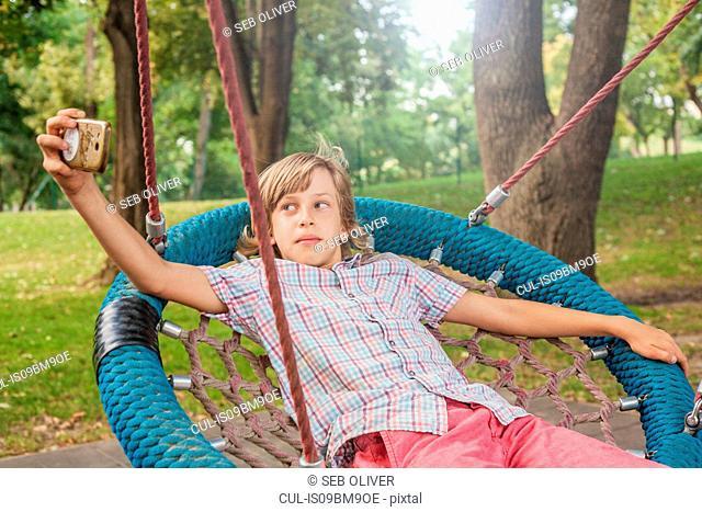 Boy taking selfie on web swing
