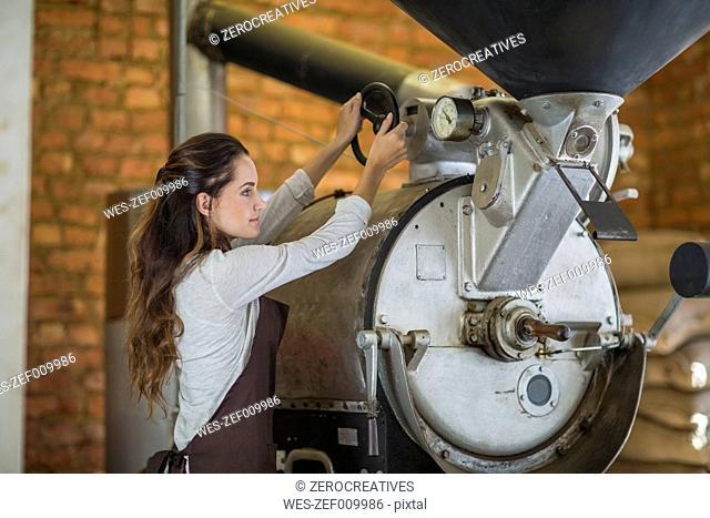 Young woman operating coffee roasting machine