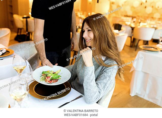 Waiter serving dish for smiling woman in a restaurant