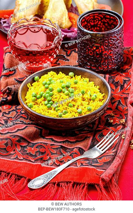 Indian cuisine, bowl of yellow rice with green peas on red background