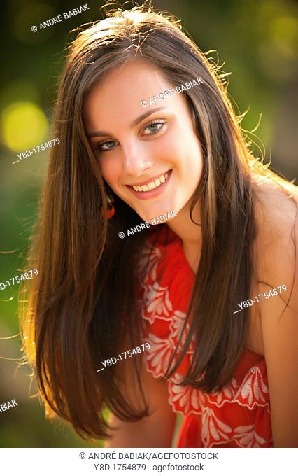 Outdoor portrait of young woman with brunette hair, 17 years old caucasian