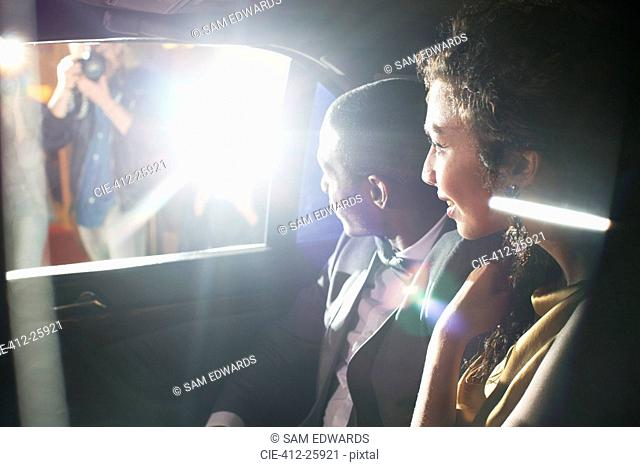 Celebrity couple in limousine arriving at red carpet event