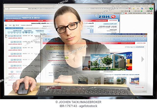 Young woman sitting at a computer surfing the Internet, booking a holiday or hotel on an online travel portal, HRS, Hotel Reservation Service