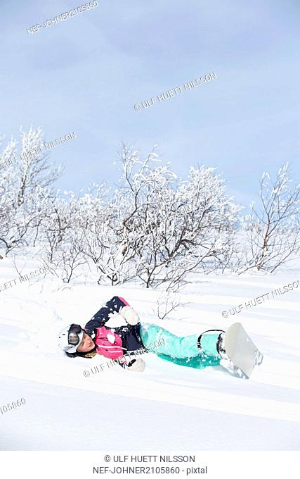 Woman with snowboard lying on snow