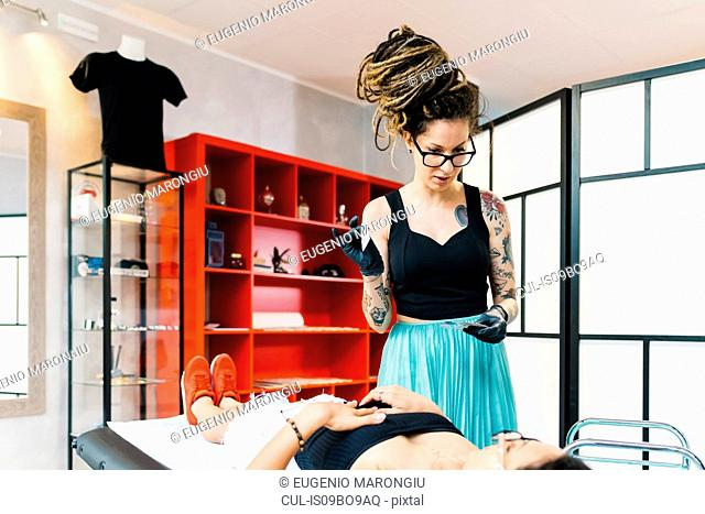 Tattooist attending to customer in parlour