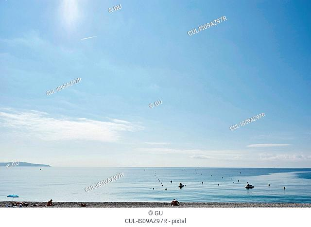 Tourists sunbathing on beach, Nice, Cote d'azur, France