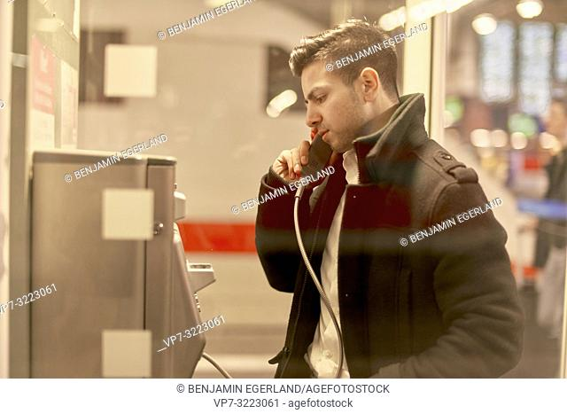 young man using telephone cabin, in Munich, Germany