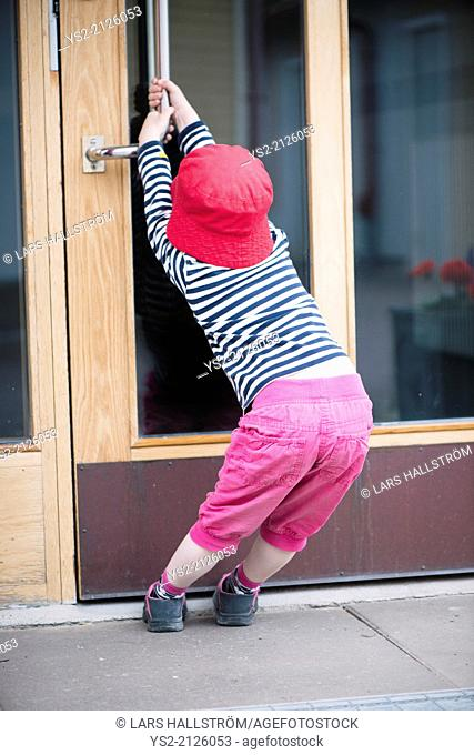 Young child struggling with heavy door, trying to open by pulling the handle