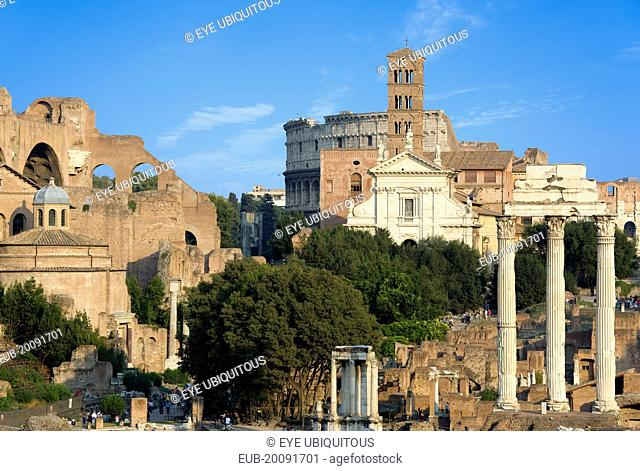 View of The Forum with the Colosseum rising behind the bell tower of the church of Santa Francesca Romana with tourists and the Temple of The Vestals and the...