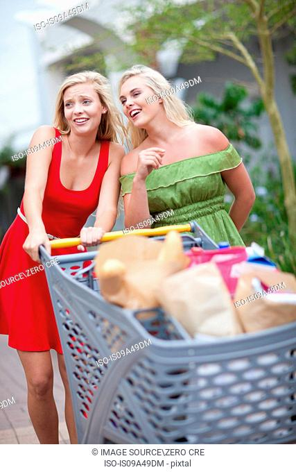 Women pushing shopping cart