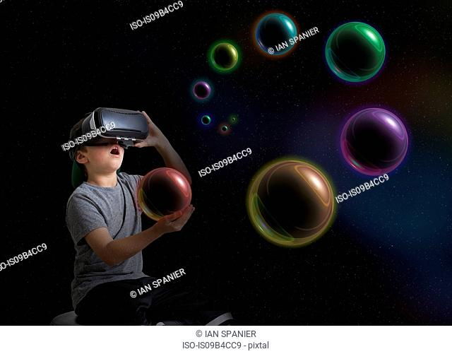 Young boy wearing virtual reality headset, holding planet in hand, digital composite