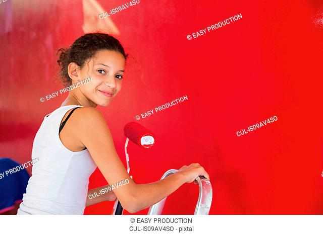 Portrait of girl on step ladder painting red wall