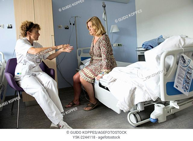 Tilburg, Netherlands. Physio therapist instructing a female post operative patient on how to walk again, after reviving a new hip in surgery