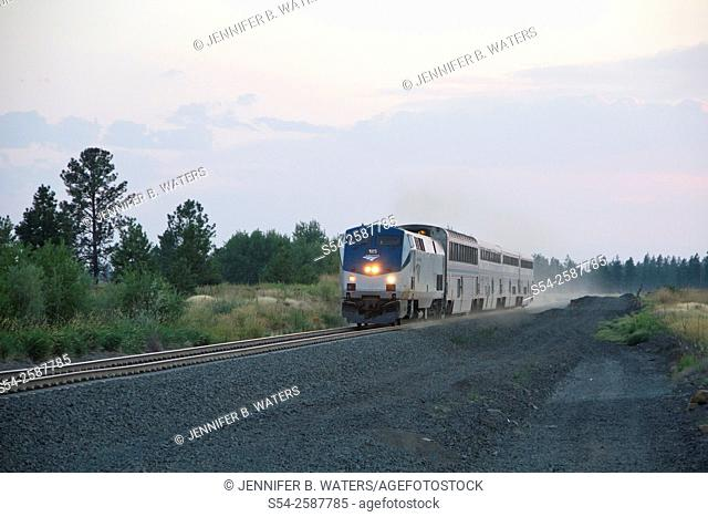 An American Amtrak passenger train travelling near Cheney, Washington, USA in the evening