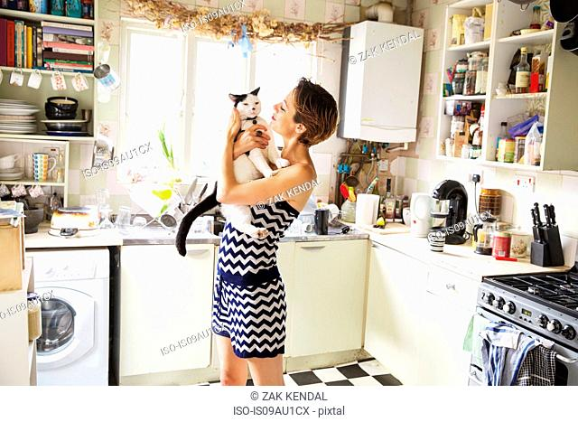 Mid adult woman carrying cat in kitchen