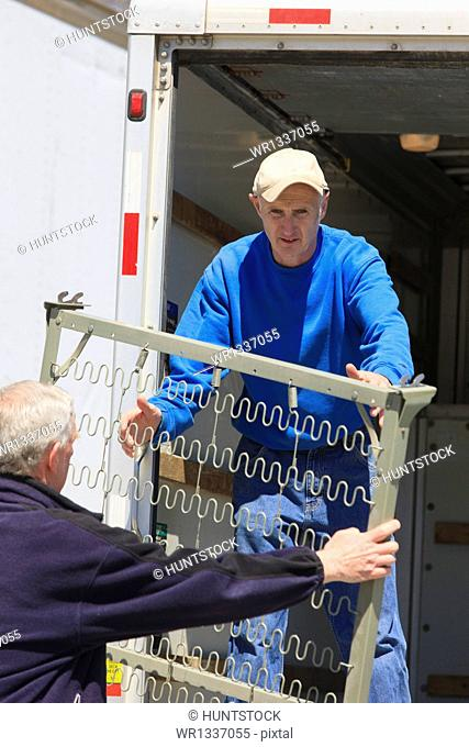 Men loading furniture into a truck