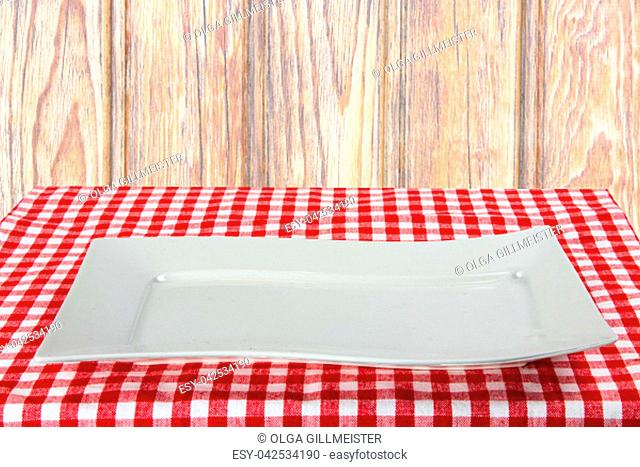 Empty white plate on red napkin over wooden background. For your food and product display montage. Concept food. Copy space