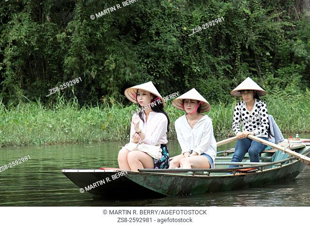 Tam Coc, Boat owners take Asian female tourists on trip along the river, Ninh Binh, Vietnam