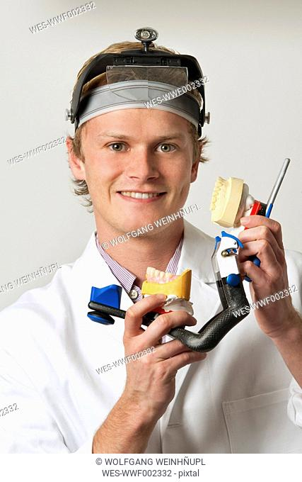 Dentist holding dentures in articulator, portrait