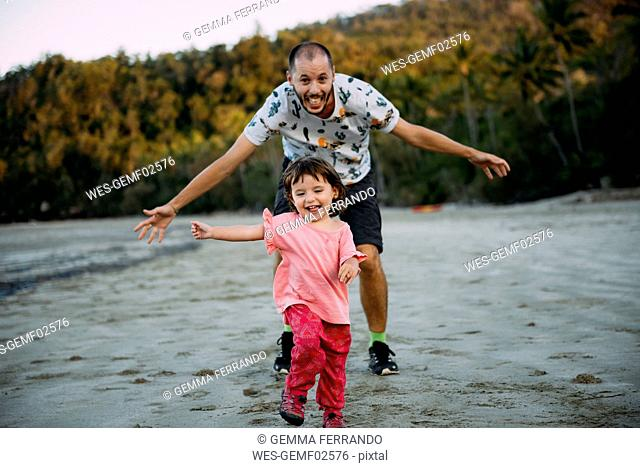 Australia, Queensland, Mackay, Cape Hillsborough National Park, happy father running after his daughter at the beach