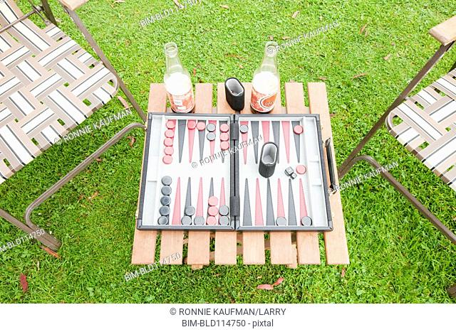 Game of backgammon with beers outdoors