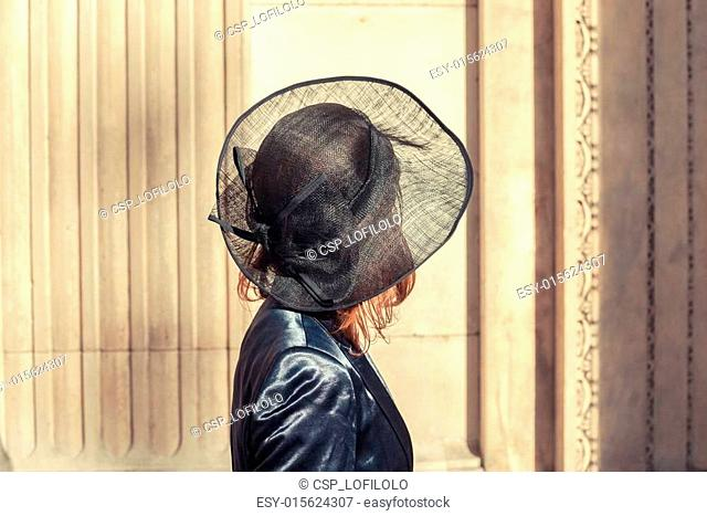 Young woman in hat admiring architecture