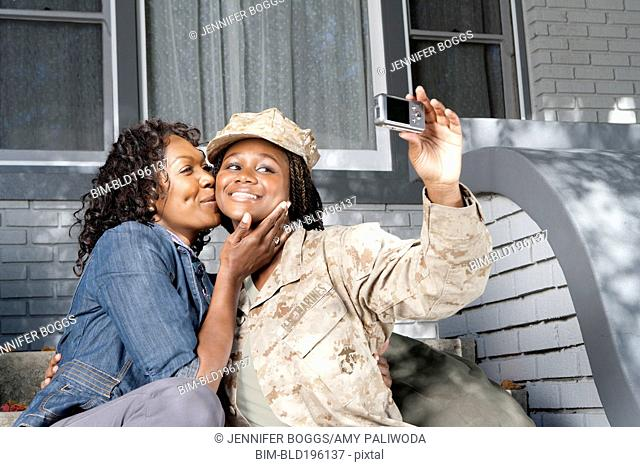 Black mother taking self-portrait with soldier daughter