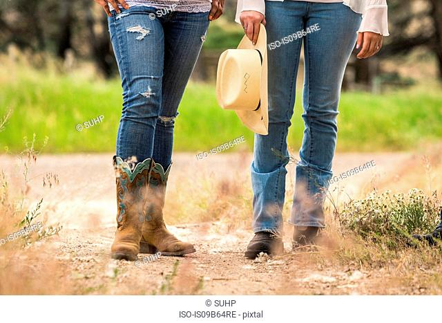 Waist down view of two young women standing on dirt track at ranch, Bridger, Montana, USA