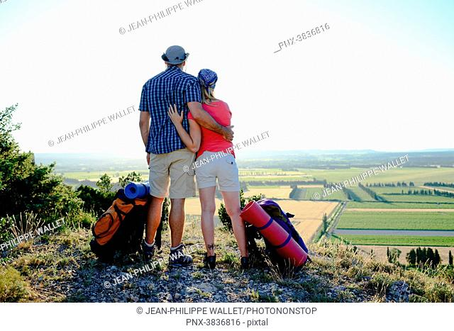 Young couple hiking on adventure trek and looking at beautiful sunset landscape