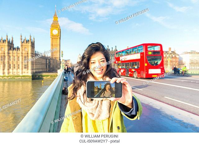 Young woman using smartphone to take selfie on Westminster bridge smiling, Thames river, London, UK