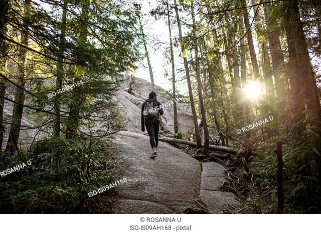 Young woman walking through forest, Squamish, British Columbia, Canada