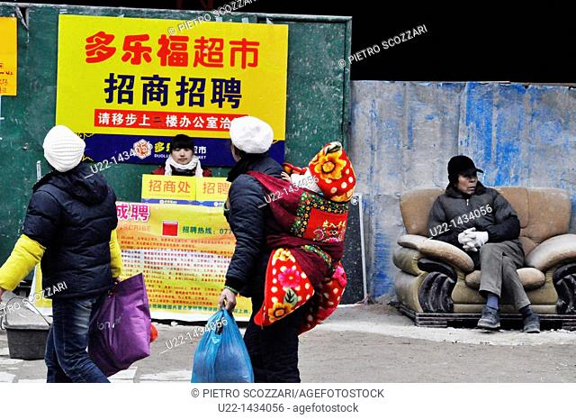 Yangshou (China): a man sitting on a couch along a sidewalk and a mother carrying her baby, at the bottom of a building construction