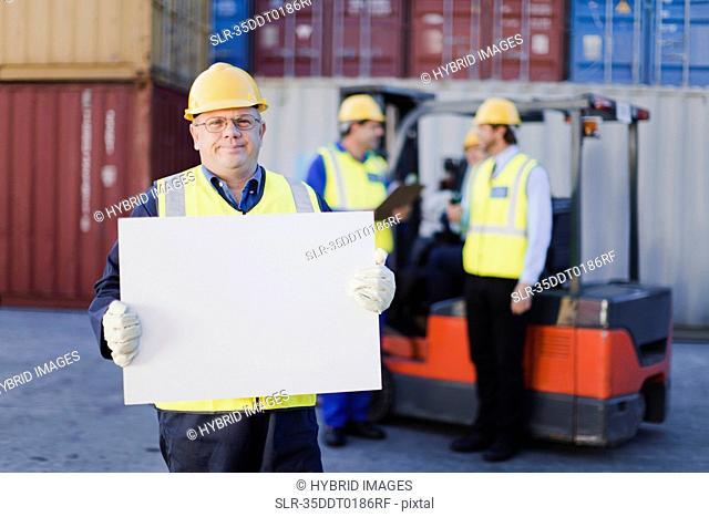 Worker holding sheet in shipping yard