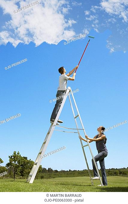 Couple painting the sky blue