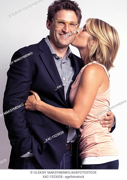 Smiling casually but with style dressed young people  Woman kissing a man on the cheek  Isolated on gray background