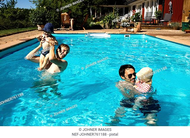 Two dads with one small children in a swimming pool, Sweden