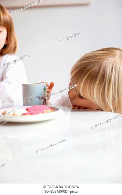 Girl leaning face on table edge looking at mug