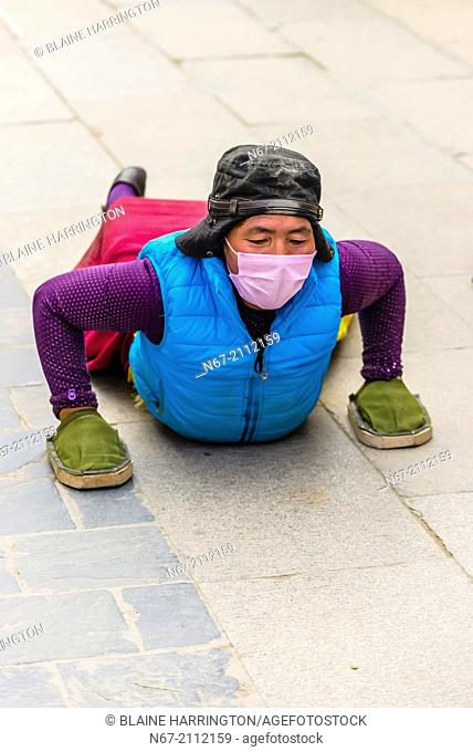 A Tibetan woman prostrates herself, as other pilgrims circumambulate The Barkhor (the route around the most sacred temple in Tibet, the Jokhang Temple), Lhasa