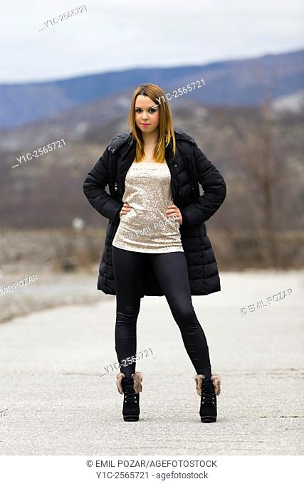 Pretty teen girl posing full length in Winter