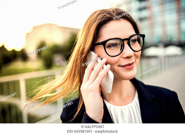 A close-up of a young businesswoman with smartphone outdoors, making a phone call
