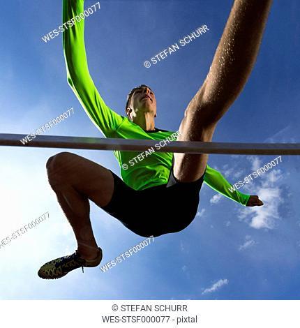 Germany, Man athlete jumping Hurdles on track
