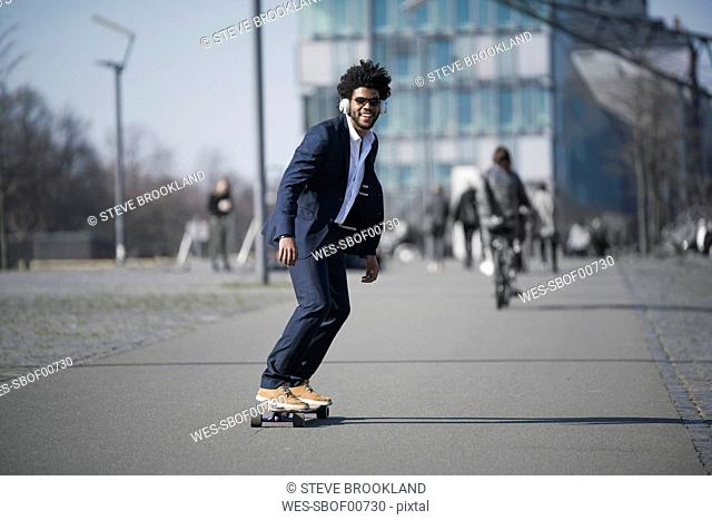 Smiling businessman riding longboard in front of skyscraper