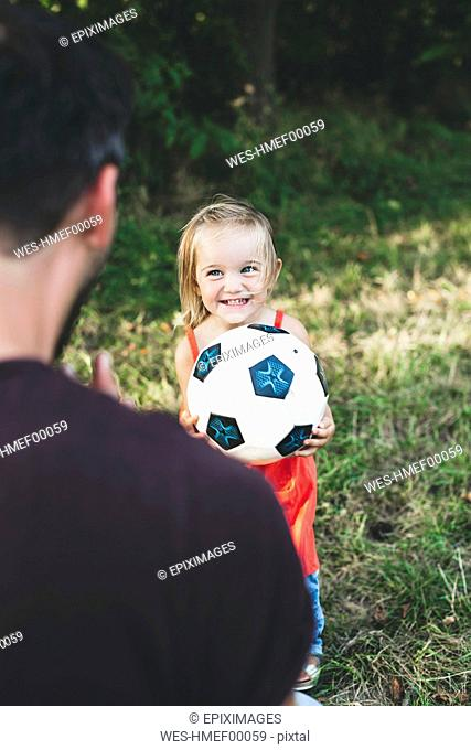 Happy girl playing football with father on meadow