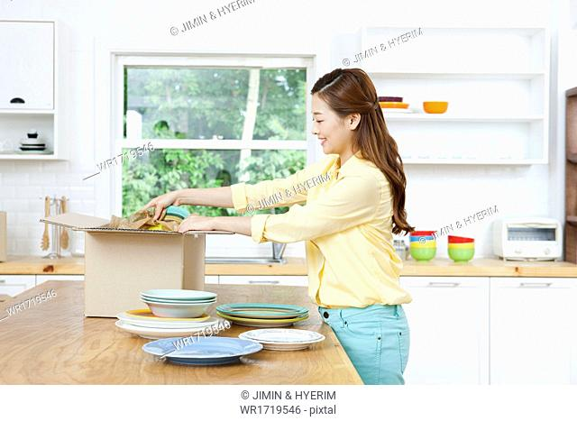A woman packing moving boxes in a kitchen