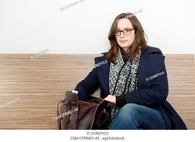 Young woman, looking up from searching for something in her purse into the camera whilst sitting on a bench in a waiting room