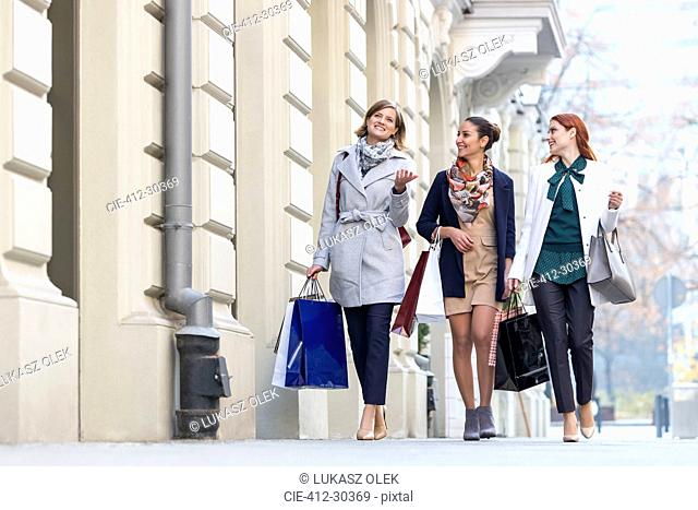 Women with shopping bags talking and walking on city sidewalk