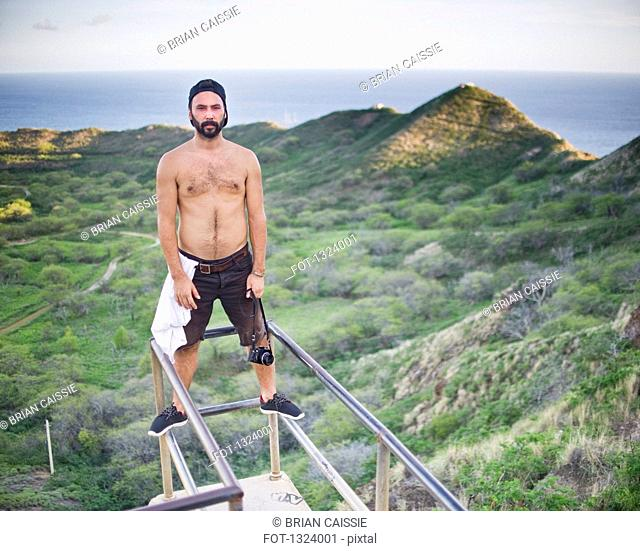 Portrait of shirtless man standing at observation point, Diamond Head Crater, Oahu, Hawaii, USA